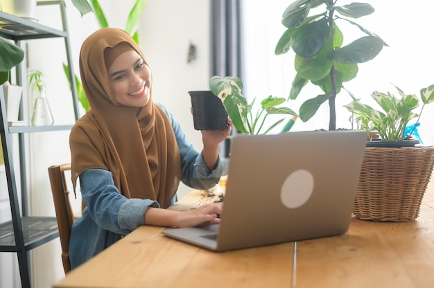 A young muslim woman entrepreneur working with laptop presents houseplants during online live stream at home, selling online concept