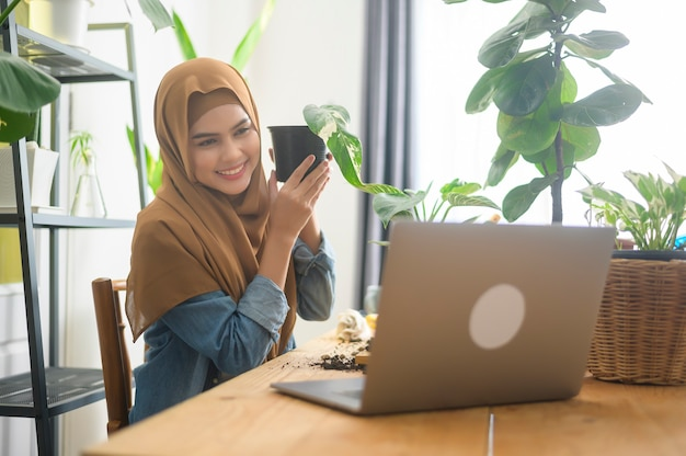 A young muslim woman entrepreneur working with laptop presents houseplants during online live stream at home