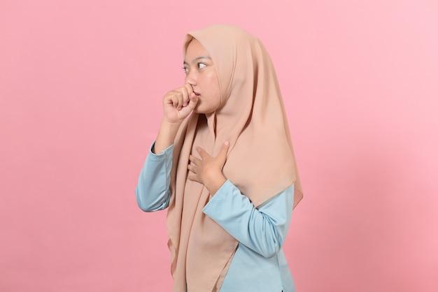 病気やインフルエンザの症状を感じている若いイスラム教徒の女性、ピンクの背景に覆われた口で咳をする