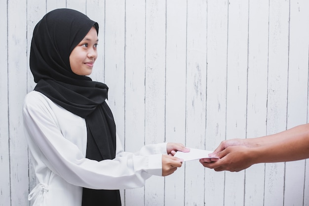 Young muslim woman giving a white envelope to give thr or pay zakat fitrah as an obligation in the holy month of ramadan