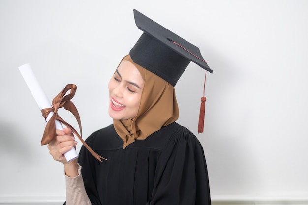 A young muslim woman graduated holding a certification.