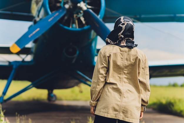 A young muslim woman in a headscarf stands against the background of an old plane.