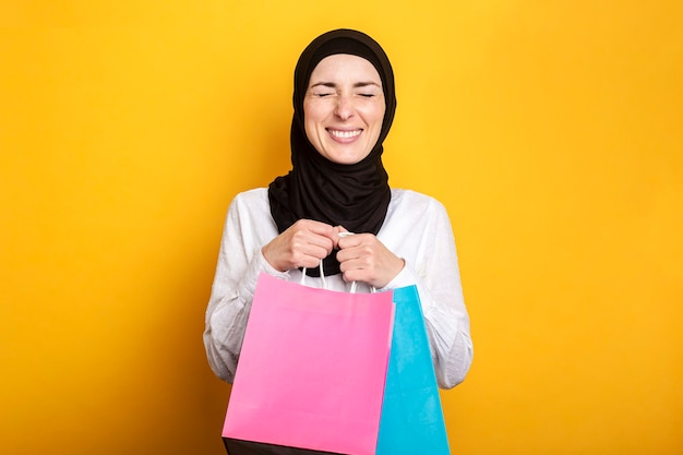 Young muslim woman in hijab holds shopping bags, closed her eyes and rejoices on a yellow