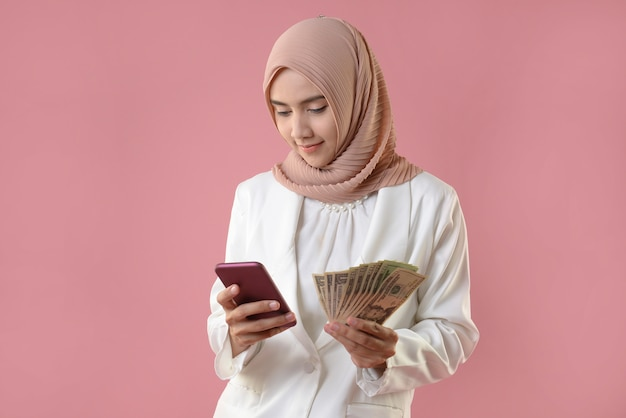 Young muslim woman hold money and smartphone