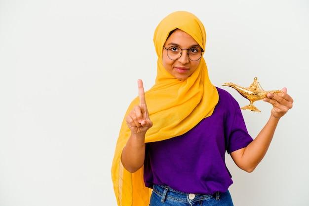손가락으로 번호 하나를 보여주는 흰 벽에 고립 된 램프를 들고 젊은 무슬림 여성.