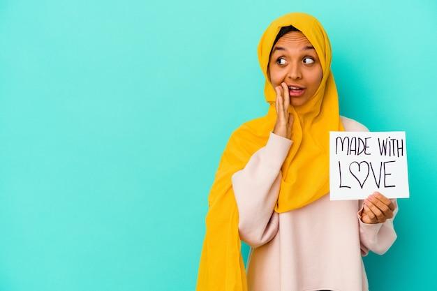 青い背景に分離された愛のプラカードで作られた若いイスラム教徒の女性は、秘密のホットブレーキニュースを言って脇を見ています