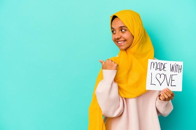 青い背景のポイントで隔離された愛のプラカードで作られた若いイスラム教徒の女性は、親指の指を離れて、笑ってのんき。