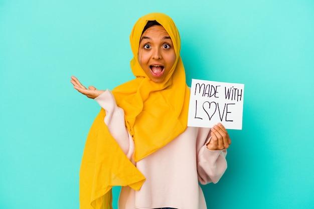 青い背景に分離された愛のプラカードで作られた若いイスラム教徒の女性は驚いてショックを受けました。