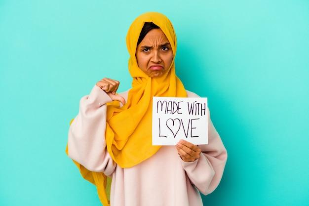 Молодая мусульманка держит плакат с любовью, изолированный на синей стене, показывает жест неприязни, пальцы вниз