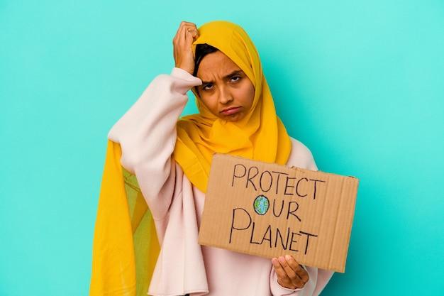 ショックを受けている青い背景で隔離された私たちの惑星を保護する保持している若いイスラム教徒の女性、彼女は重要な会議を覚えています。