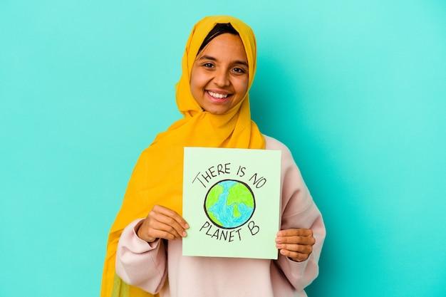 そこを保持している若いイスラム教徒の女性は幸せ、笑顔、陽気な青い背景に分離された惑星bプラカードはありません。