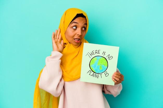 Молодая мусульманская женщина, держащая не планету b, изолирована на синем фоне, пытаясь слушать сплетни.