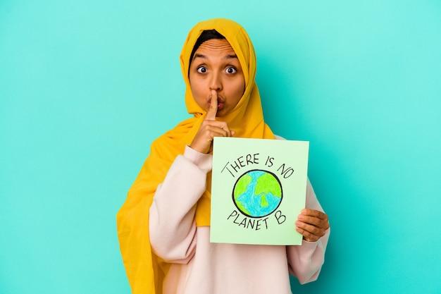 Молодая мусульманка держит плакат с надписью `` нет планеты b '' на синей стене, хранящей в секрете или просящей тишины