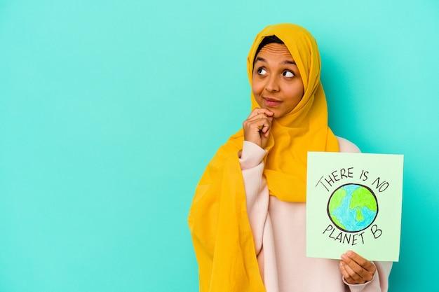 젊은 무슬림 여성이 들고있는 행성 b 플래 카드는 의심스럽고 회의적인 표정으로 옆으로 보이는 파란색 벽에 고립 된 플래 카드가 없습니다.