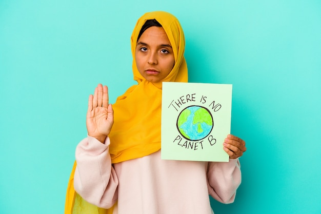 들고 젊은 무슬림 여성은 정지 신호를 보여주는 뻗은 손으로 서 파란색 벽에 고립 된 행성 b 플래 카드가 없습니다