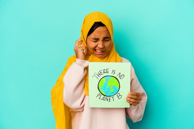 Молодая мусульманская женщина, держащая плакат с надписью `` нет планеты b ''