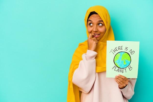 젊은 무슬림 여성이 복사 공간을보고 뭔가에 대해 파란색 편안한 생각에 행성 b 플래 카드가 없습니다.