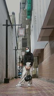 마스크를 쓰고 가방을 들고 있는 젊은 이슬람 여성