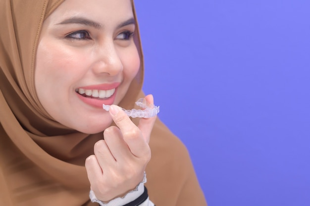 A young muslim woman holding invisalign braces in studio, dental healthcare and orthodontic concept.
