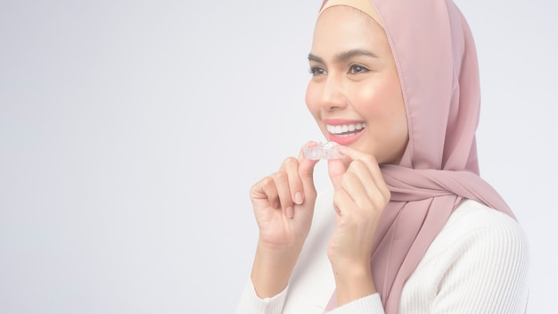 A young muslim woman holding invisalign braces over white background studio, dental healthcare and orthodontic concept.