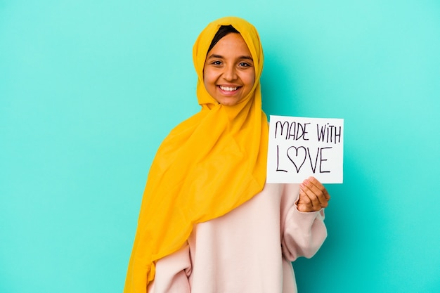 Young muslim woman holding a made with love placard isolated on blue background happy, smiling and cheerful.