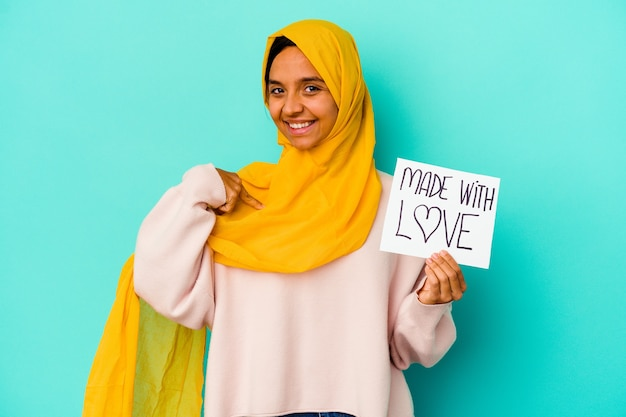 Young muslim woman holding a made with love placard isolated on blue background person pointing by hand to a shirt copy space, proud and confident