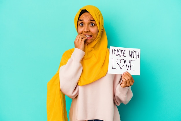 Young muslim woman holding a made with love placard isolated on blue wall biting fingernails, nervous and very anxious.