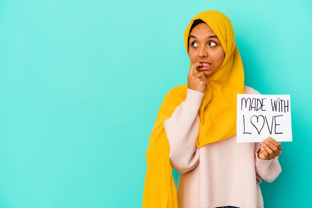 Young muslim woman holding a made with love placard isolated on blue wall relaxed thinking about something looking at a copy space.