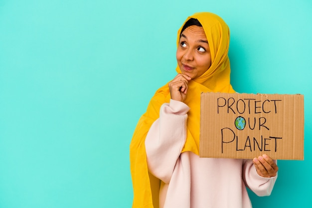 Young muslim woman holding a protect our planet isolated on blue background looking sideways with doubtful and skeptical expression.