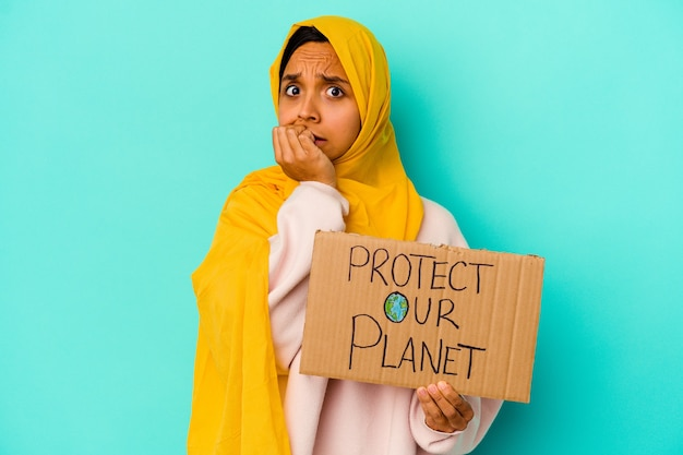 Young muslim woman holding a protect our planet isolated on blue wall biting fingernails, nervous and very anxious