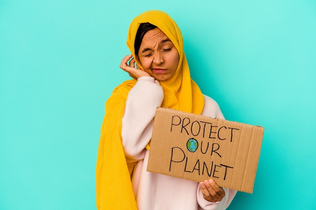Young muslim woman holding a protect our planet isolated on blue wall covering ears with hands.