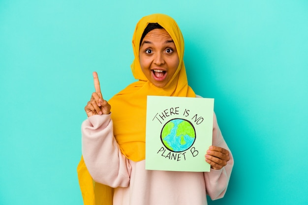 Young muslim woman holding a there is not planet b placard  isolated on blue background having some great idea, concept of creativity.