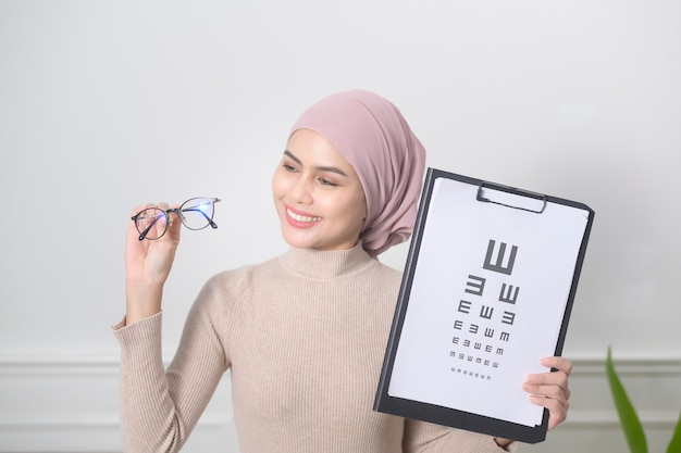 A young muslim woman holding a vision chart test for measuring visual acuity