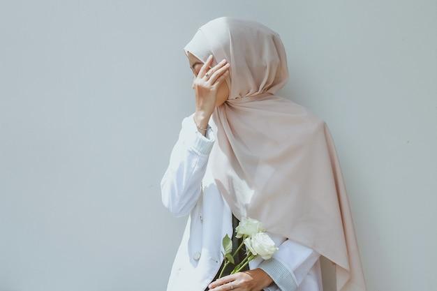 白いバラを保持し、手で顔を覆う若いイスラム教徒の女性