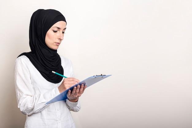 白いシャツとヒジャーブの若いイスラム教徒の女性はクリップボードを保持し、メモを取る