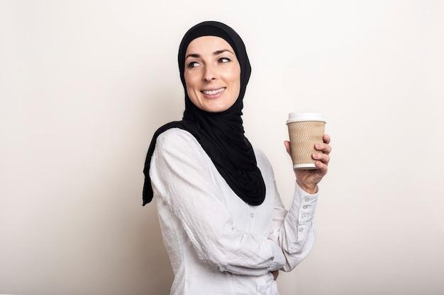 흰 셔츠와 미소로 hijab에 젊은 무슬림 여성은 커피와 함께 종이 컵을 보유