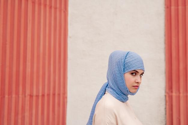 壁に建物の壁と青いヒジャーブ立っている若いイスラム教徒の女性