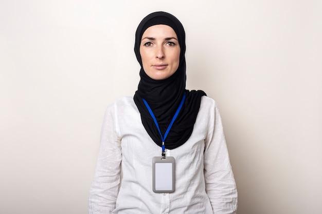 사무실 배지와 흰 셔츠와 hijab에 젊은 무슬림 여성