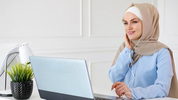 若いイスラム教徒の女性はラップトップを使用してイヤホンで音楽を聴いて楽しんでいます