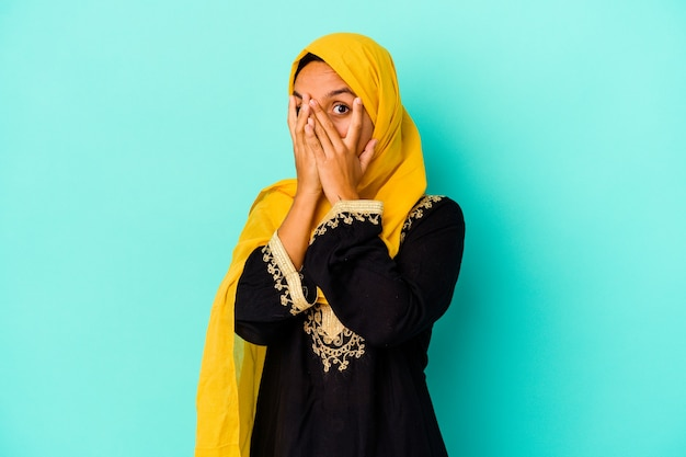 Young muslim woman isolated on blue background blink through fingers frightened and nervous.