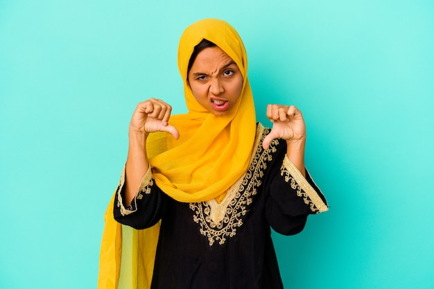 Young muslim woman isolated on blue background showing thumb down and expressing dislike.
