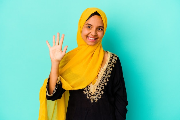 Young muslim woman isolated on blue background smiling cheerful showing number five with fingers.