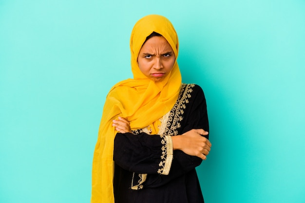 Young muslim woman isolated on blue wall frowning face in displeasure, keeps arms folded