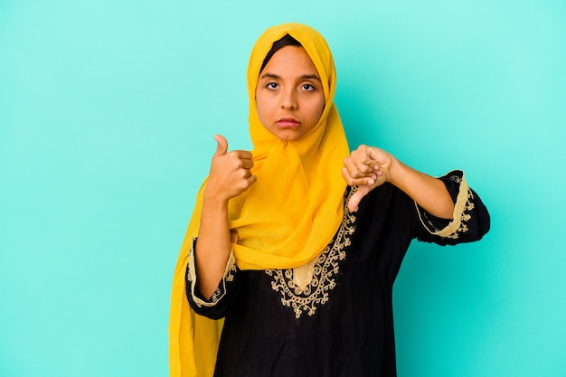 Young muslim woman isolated on blue wall showing thumbs up and thumbs down, difficult choose concept