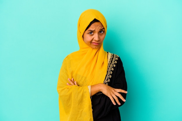 Young muslim woman isolated on blue wall unhappy looking in camera with sarcastic expression