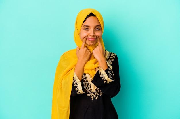 2つのオプションの間で疑う青い背景に分離された若いイスラム教徒の女性。