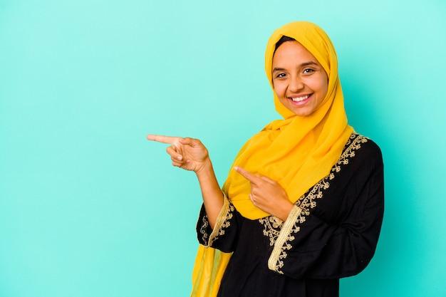 青い背景に孤立した若いイスラム教徒の女性は、人差し指を離れて指して興奮しました。