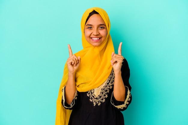 파란색 배경에 고립 된 젊은 무슬림 여성은 빈 공간을 보여주는 두 앞 손가락으로 나타냅니다.