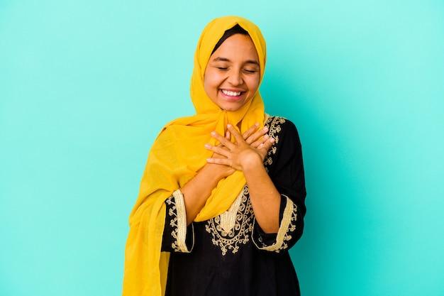 青の背景に孤立した若いイスラム教徒の女性は、心に手を置いて笑って、幸せの概念。