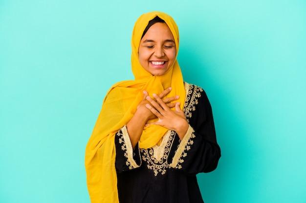 青い背景に孤立した若いイスラム教徒の女性は、胸に手を置いて大声で笑います。 Premium写真